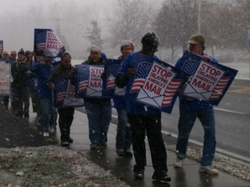 Postal employees and retirees protested to try to get the Postmaster General to accept Congress' moratorium which would delay the closure of 82 post offices for one year. (c) Waldy Diez 2014