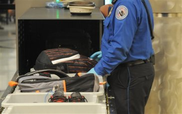 A Transportation Security Administration officer goes through carry on luggage coming out the X-ray scanner at the security checkpoint at Hartsfield-Jackson Atlanta International Airport on Wednesday August 3, 2011 in Atlanta. The TSA was created after the terrorist attacks of Sept. 11, 2001. (AP Photo/Erik S. Lesser)